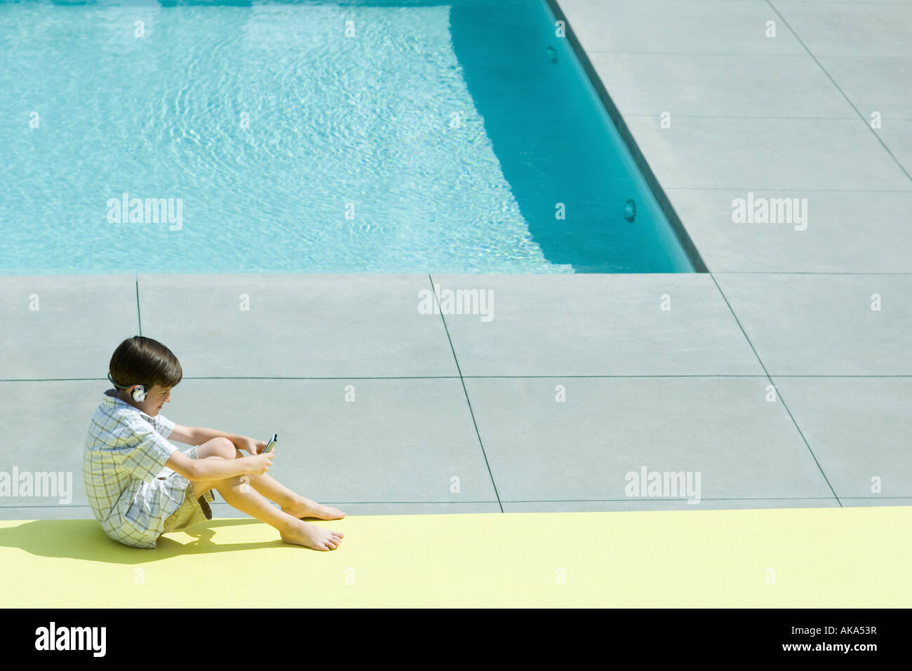 Boy sitting on the ground next to swimming pool, using handheld electronic device, wearing headphones - Stock Image