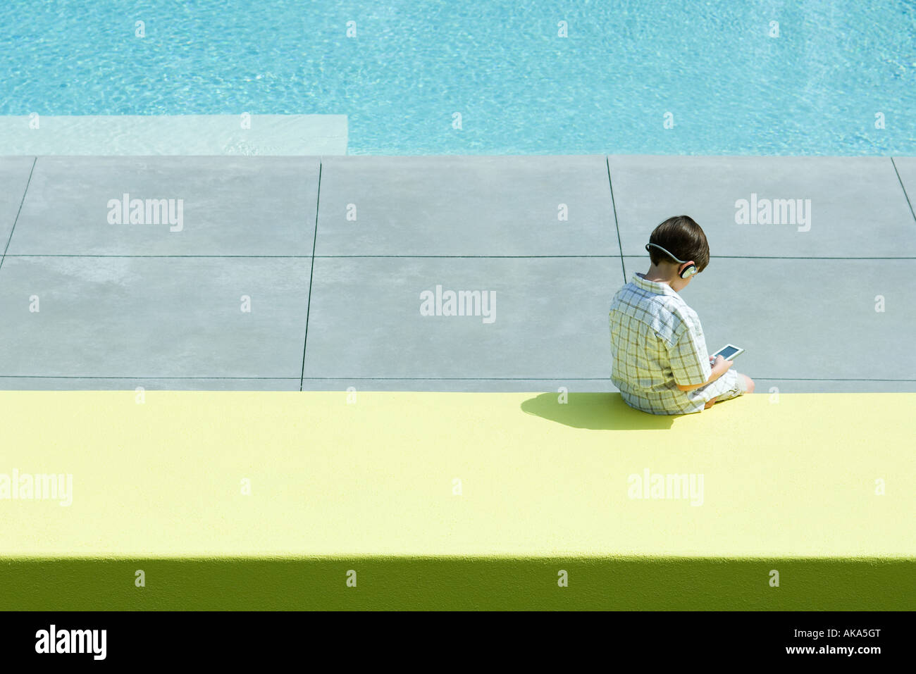 Boy sitting by swimming pool, using handheld electronic device, wearing headphones, rear view Stock Photo