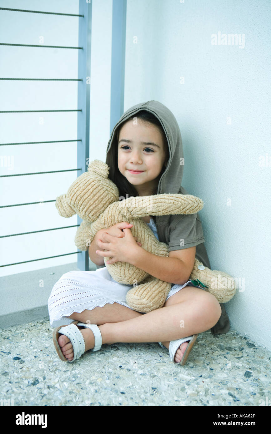 Little girl sitting on floor, holding teddy bear, smiling, full length - Stock Image