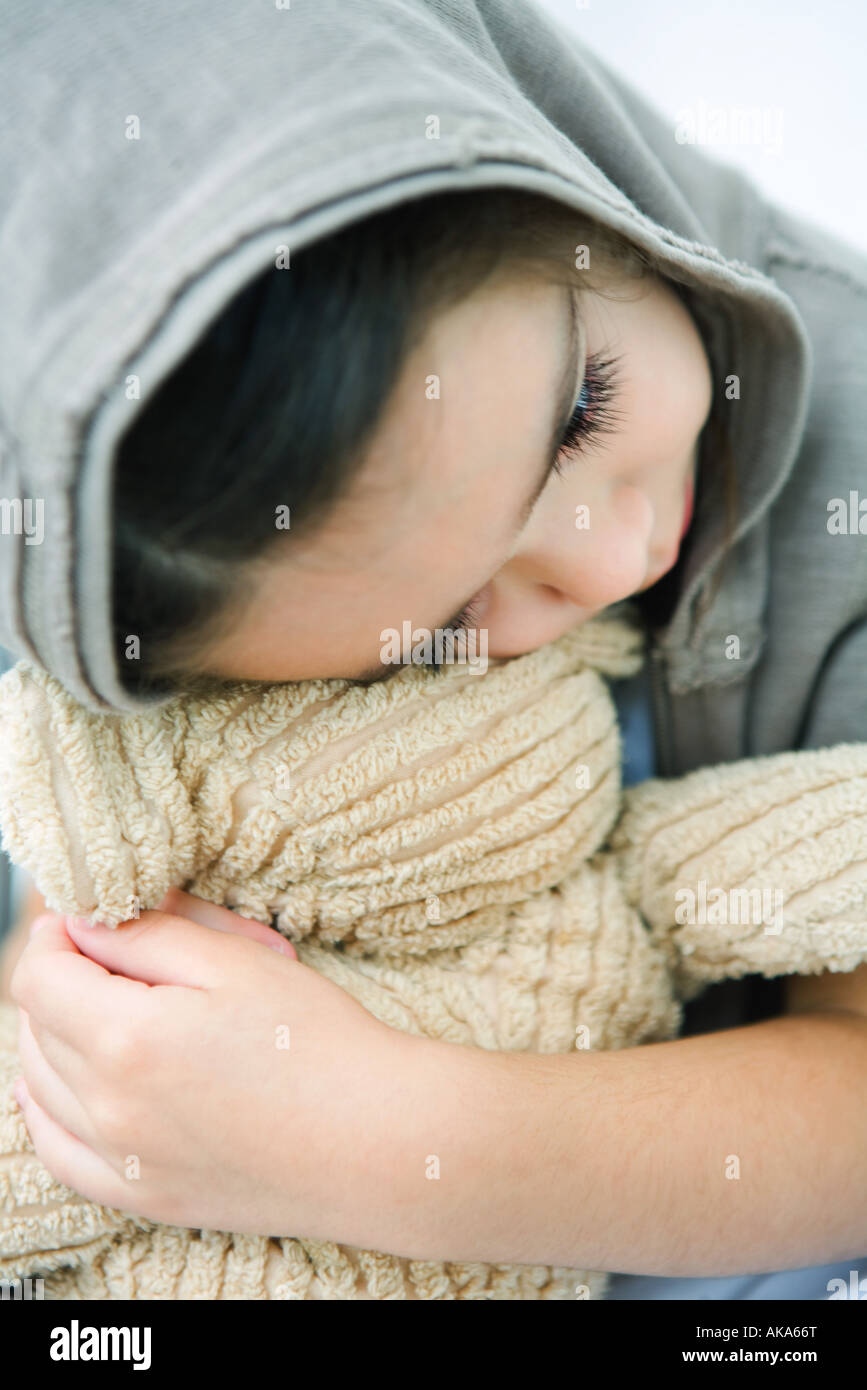 Little girl resting head on teddy bear, close-up - Stock Image