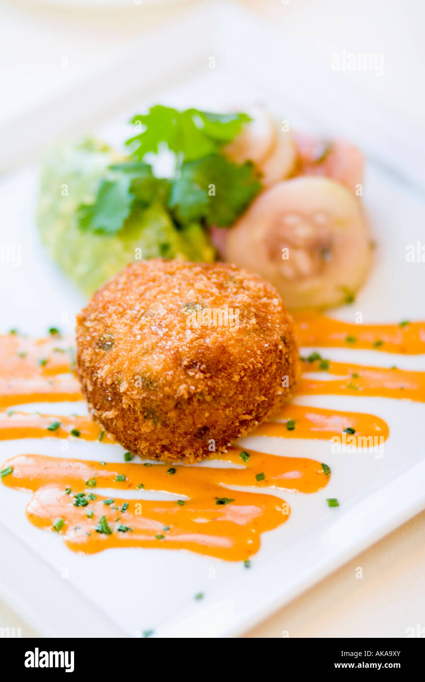 Crispy fish cake with tangy sauce and salad - Stock Image