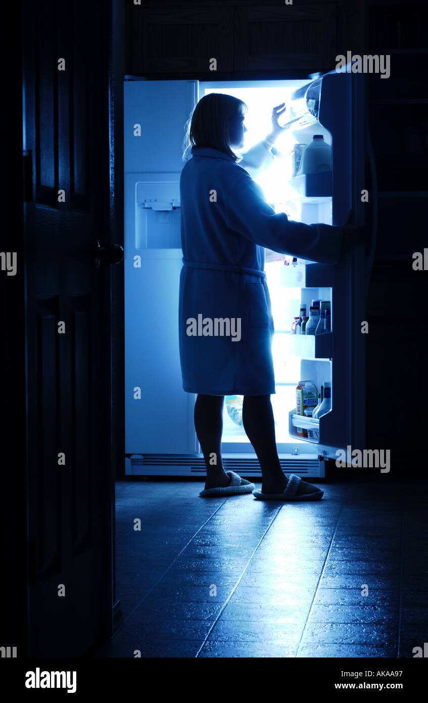 Woman opening refrigerator for a midnight snack - Stock Image
