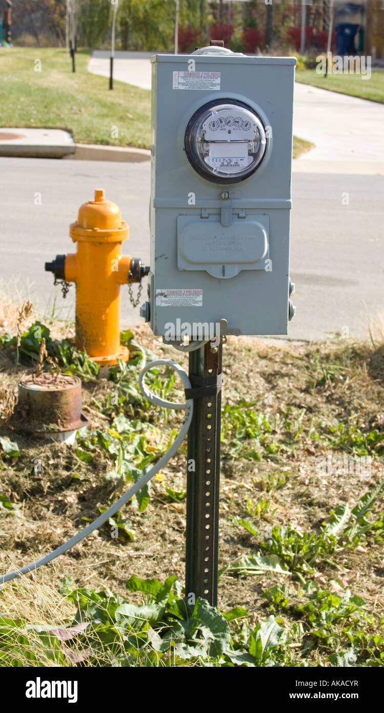 This is a picture of a fire hydrant and an electric meter. - Stock Image