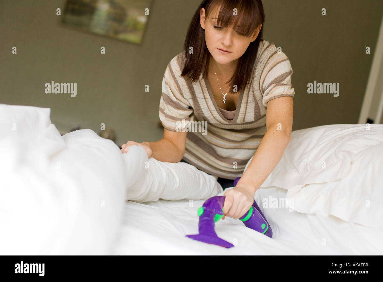 woman hoovering bed to kill bed bugs - Stock Image