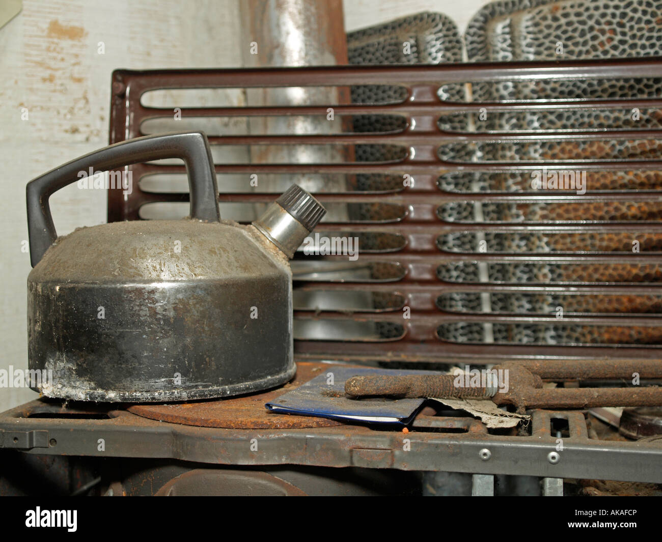 old dirty rusty water kettle on an old oil oven - Stock Image