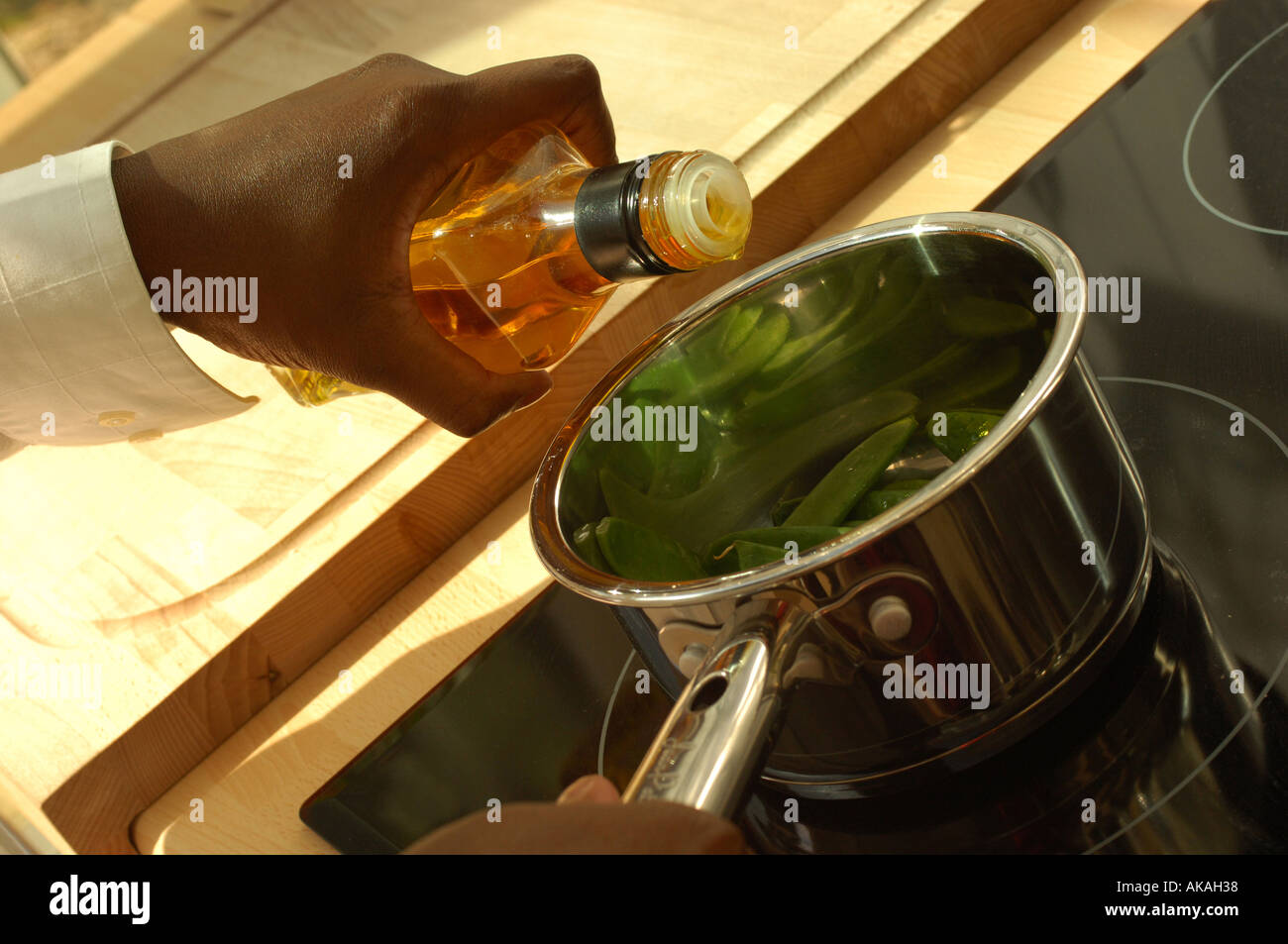 Black womans hand with saucepan of mange tout and olive oil - Stock Image