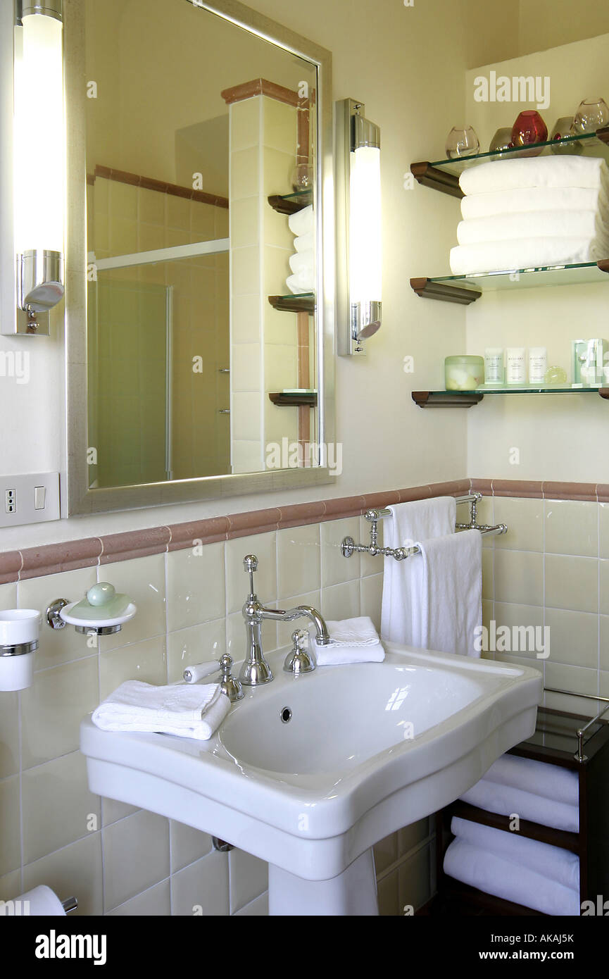 Bathroom Sink With Silver Taps White Tiles Shelves With White Towels Face  Cloths Candles And The Shower Reflected In The Mirror