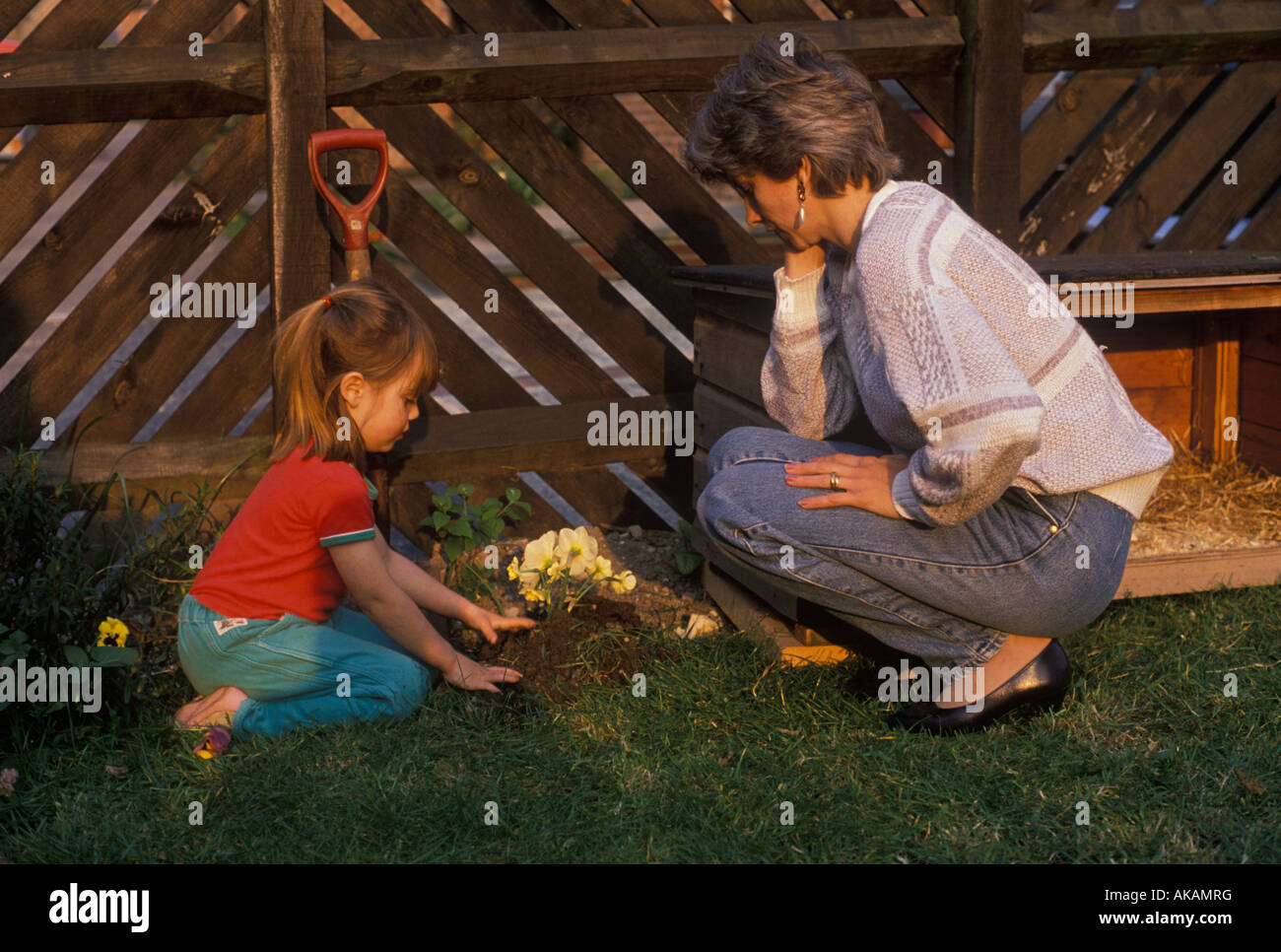 mother and daughter burying a pet - Stock Image