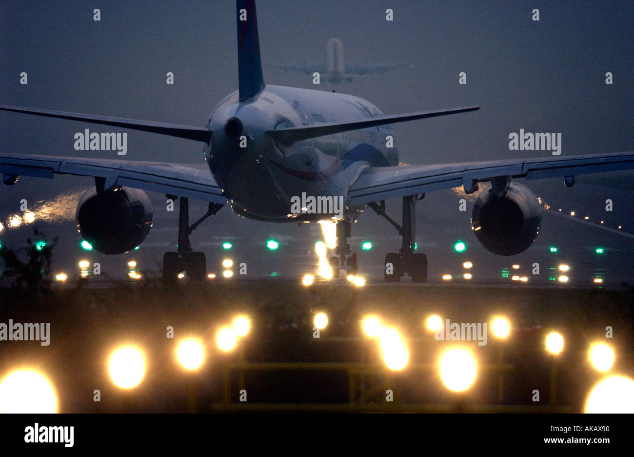 A First Choice plane prepares for takeoff from Gatwick at night moments after another jet leaves the runway - Stock Image