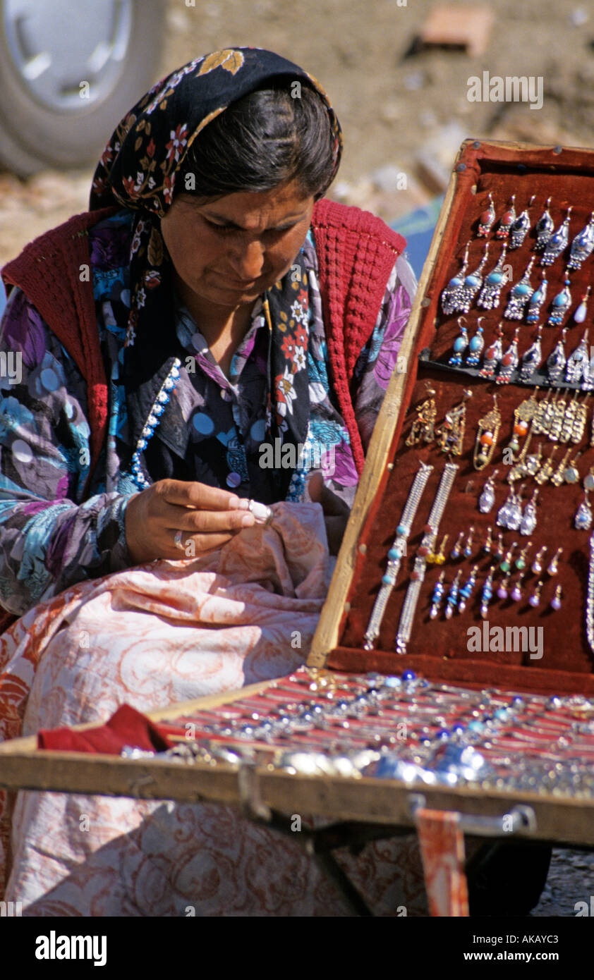Local women in colorful traditional clothes sewing tapestry and selling jewellery Turkey - Stock Image