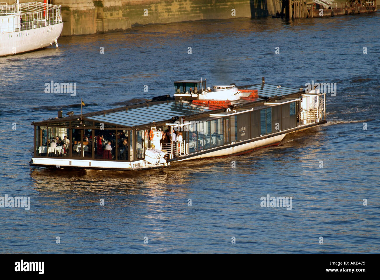 London River Thames Bateaux Mouches style tour boat Symphony with people at tables and captain at the helm - Stock Image