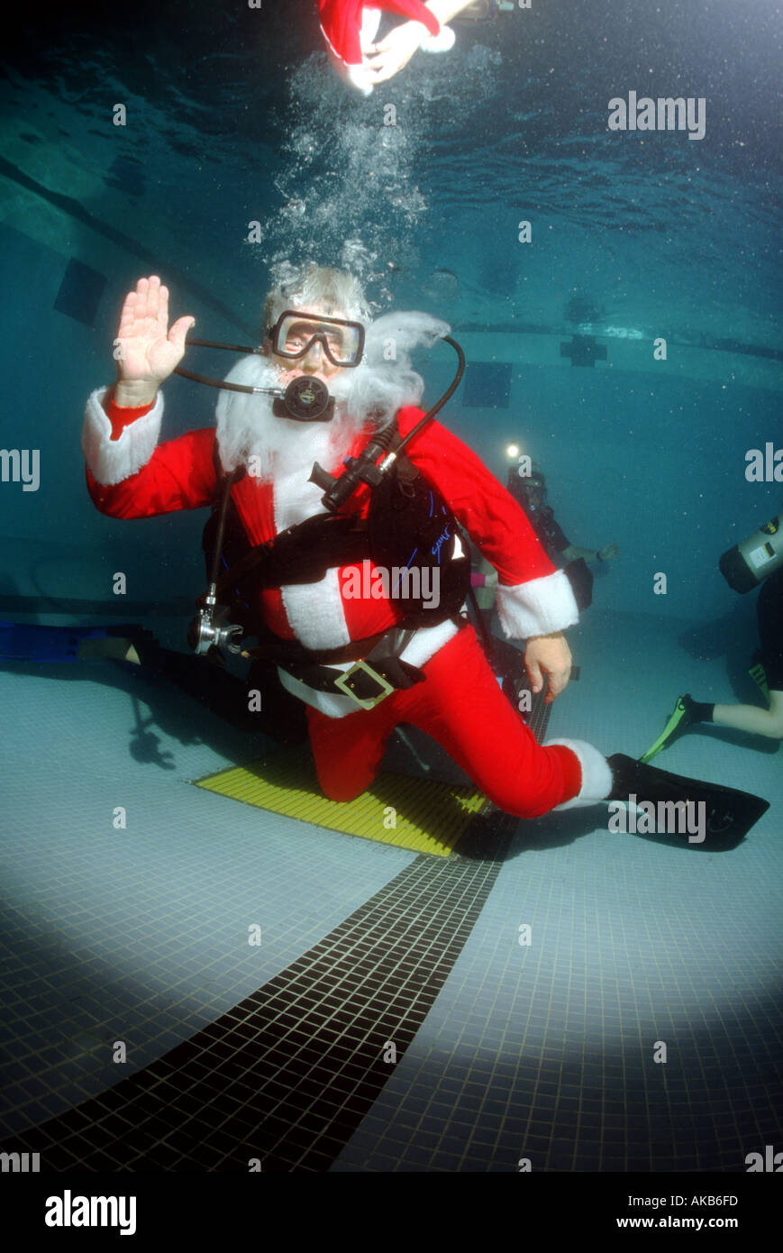 In this YMCA pool Santa Claus swims waves and loses his hat but still enjoys the holiday spirit on scuba - Stock Image