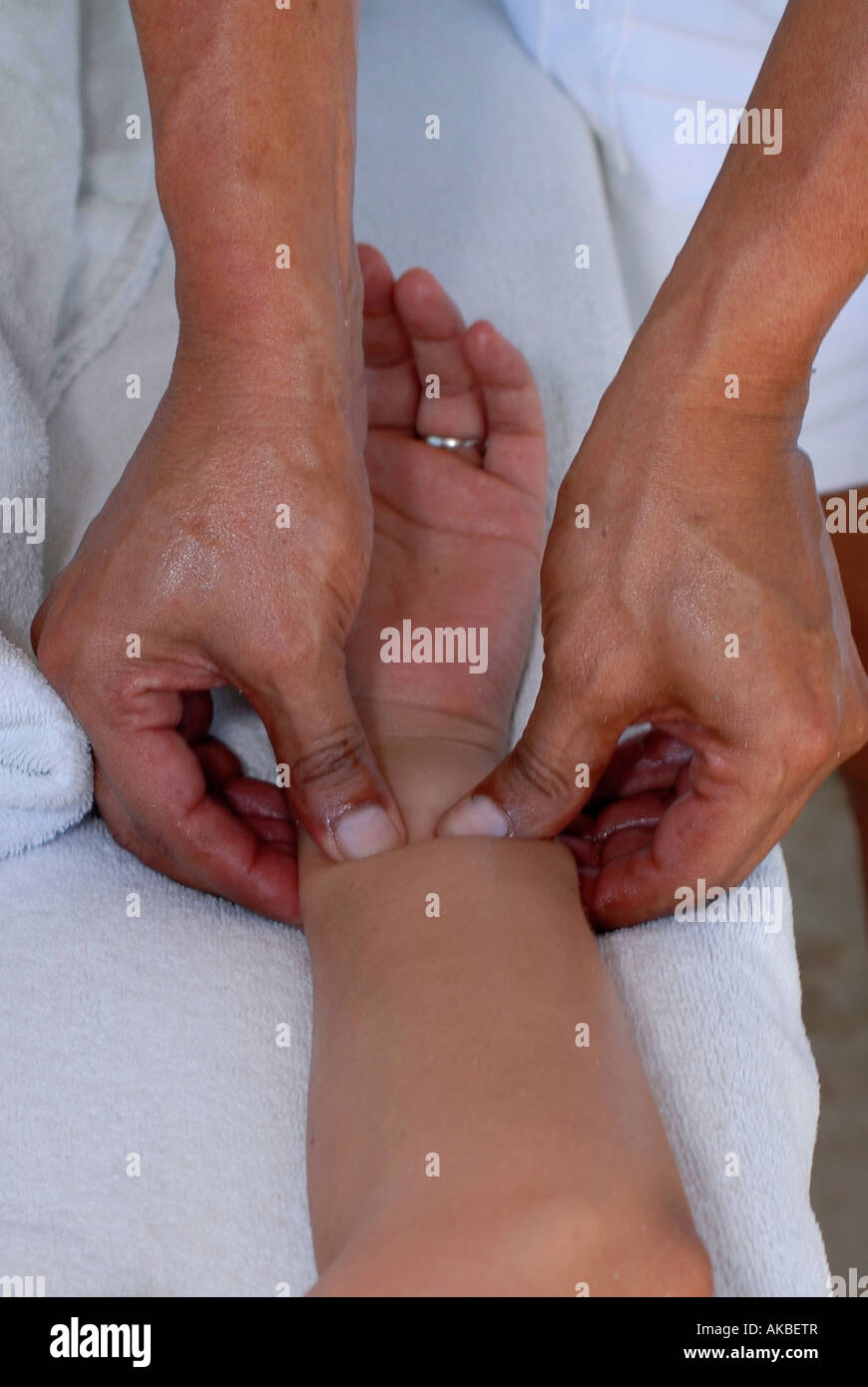 Finger pressure point on a wrist during a massage session - Stock Image