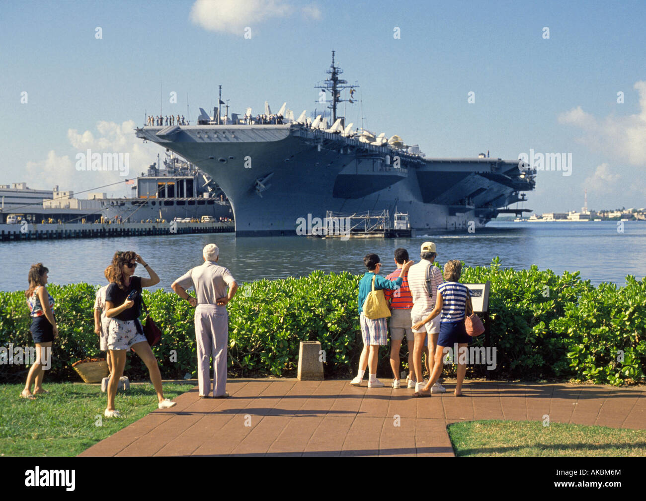 Visitors look at an American Aircraft Carrier moored at Pearl Harbor Stock Photo