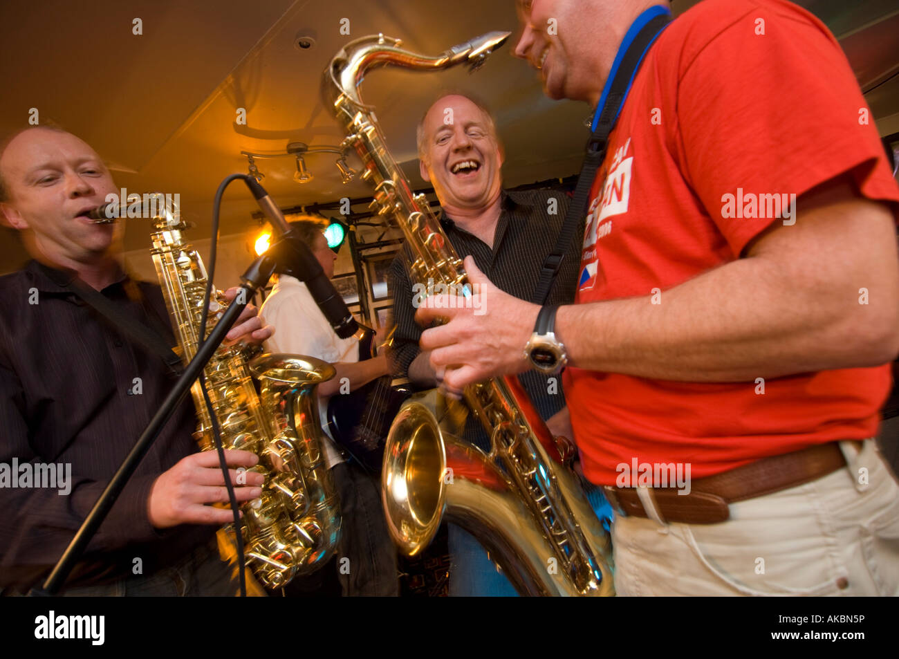 Three happy smiling laughing male Jazz musicians playing music in a nightclub - Stock Image
