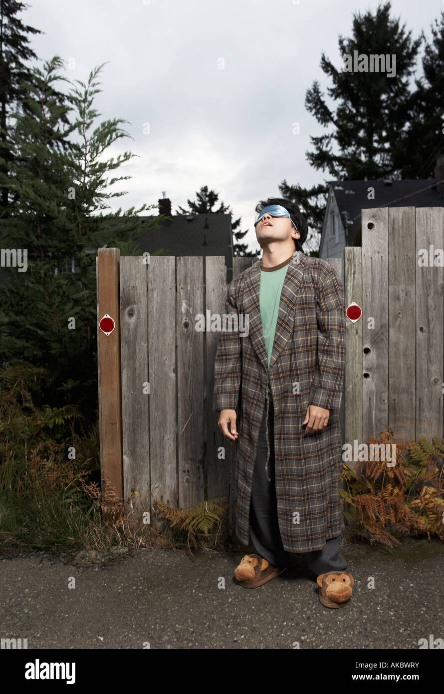 Sleepwalking man snoozing next to fence - Stock Image