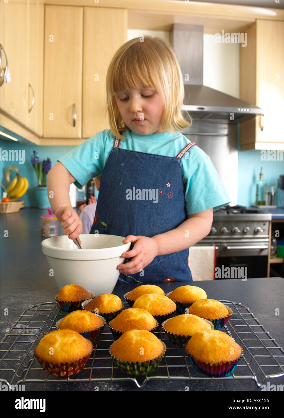 Children cooking cakes in their kitchen at home - Stock Image