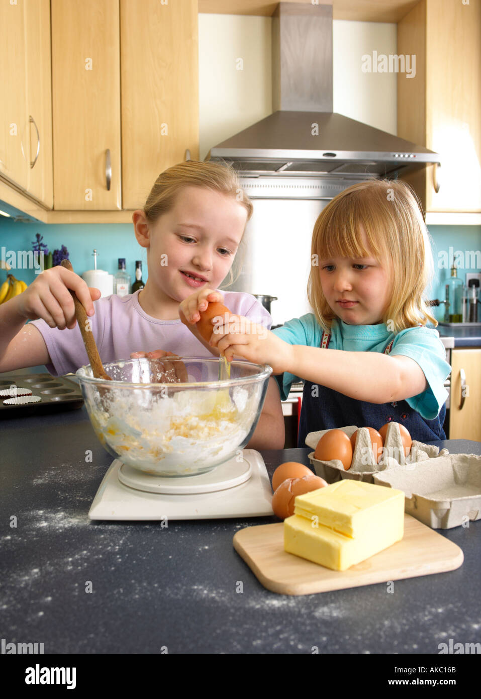Children cooking cakes in the kitchen at home - Stock Image