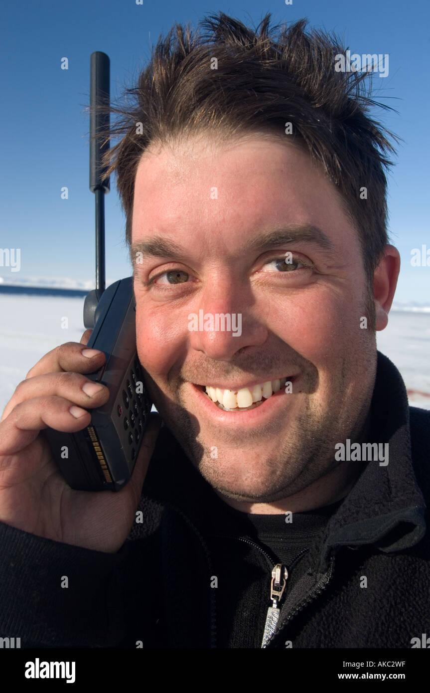 Qaanaaq Greenland Graham Dickson Using iridium satellite phone in the high Arctic Stock Photo