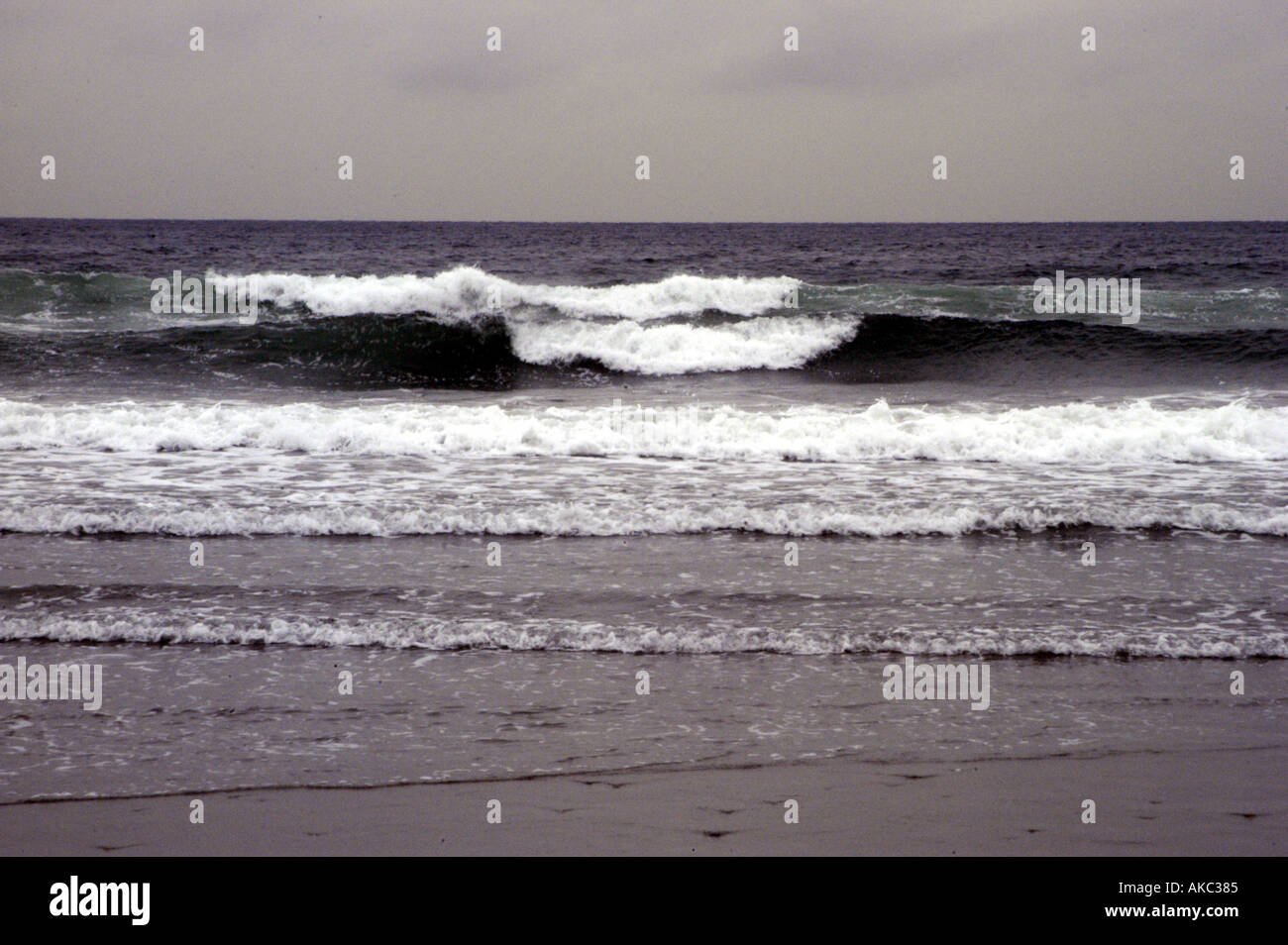 Waves breaking on cloudy dreary day - Stock Image