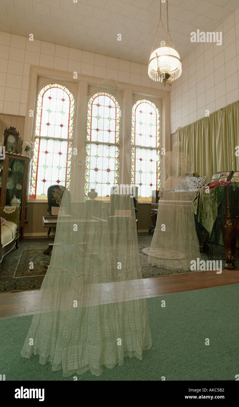 Interior of Heritage Museum in Independence Oregon USA double exposed to make a white dress look like a ghostly figure - Stock Image