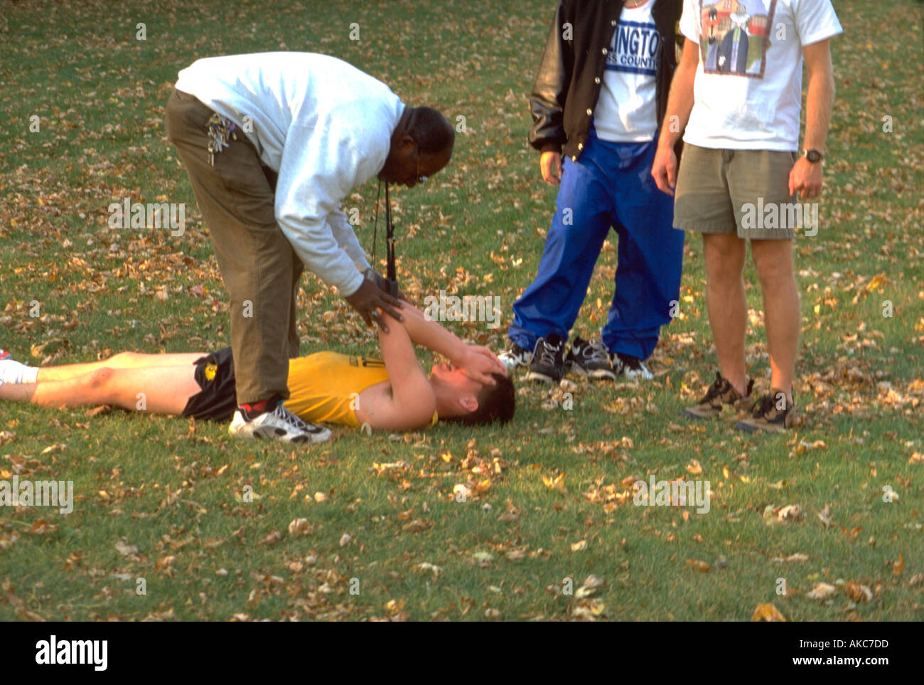 Coach 41 helping injured runner 16 at cross-country regional's. St Paul Minnesota USA - Stock Image