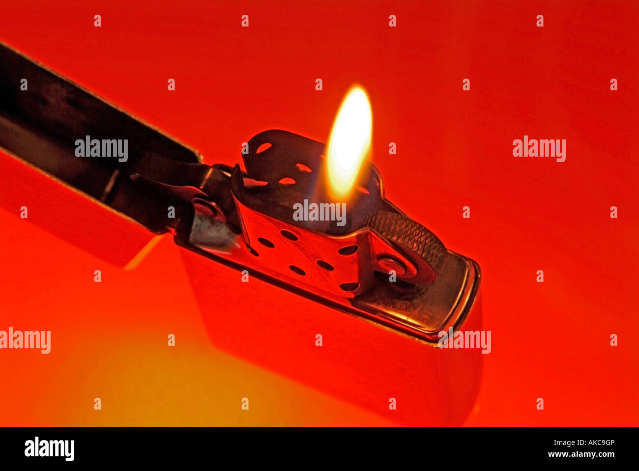 cigarette lighter Zippo with burning flame against red background - Stock Image