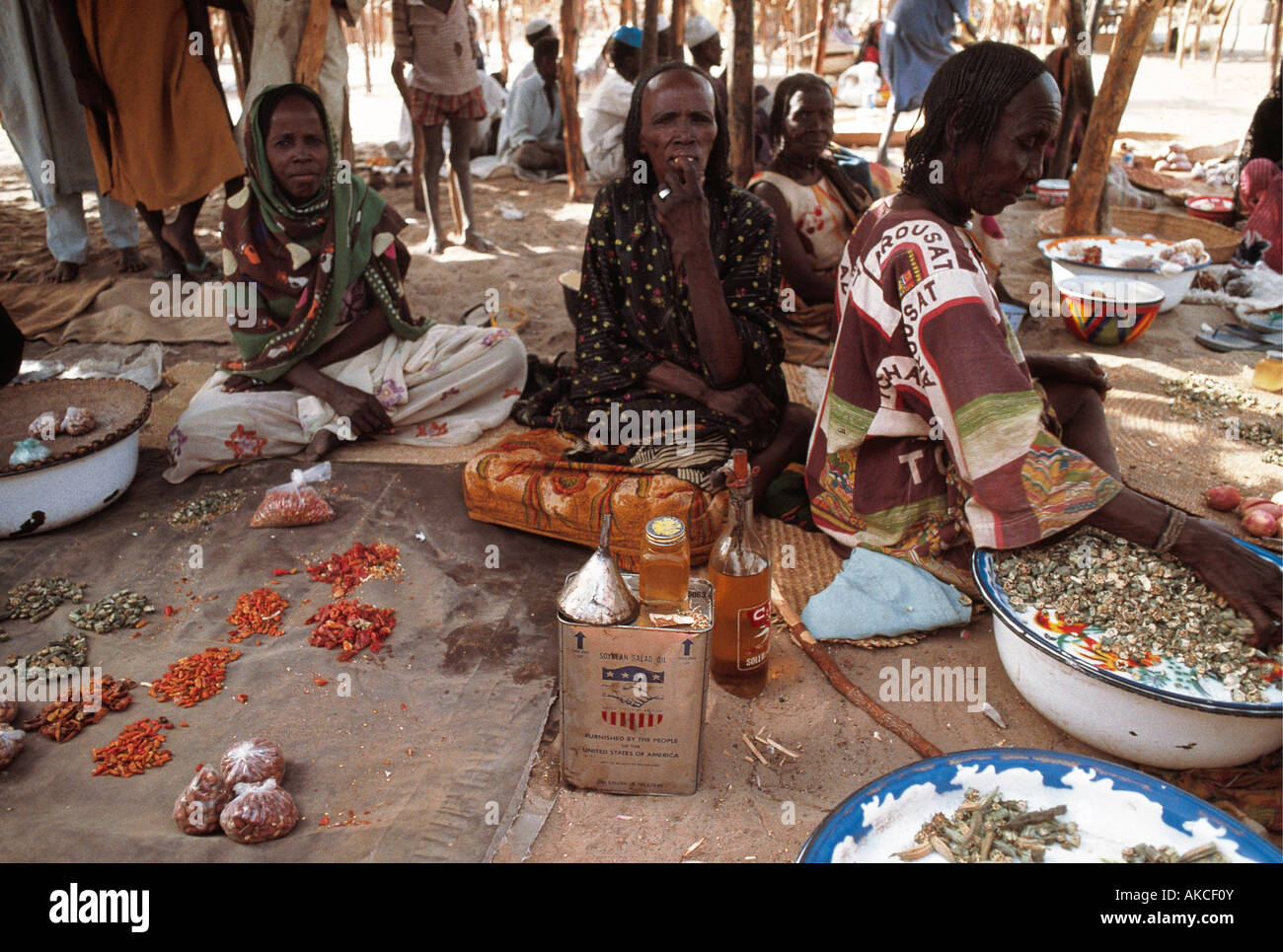 Four African women squatting on mats and cushions to sell their wares in Bol market Lake Chad Chad Africa - Stock Image