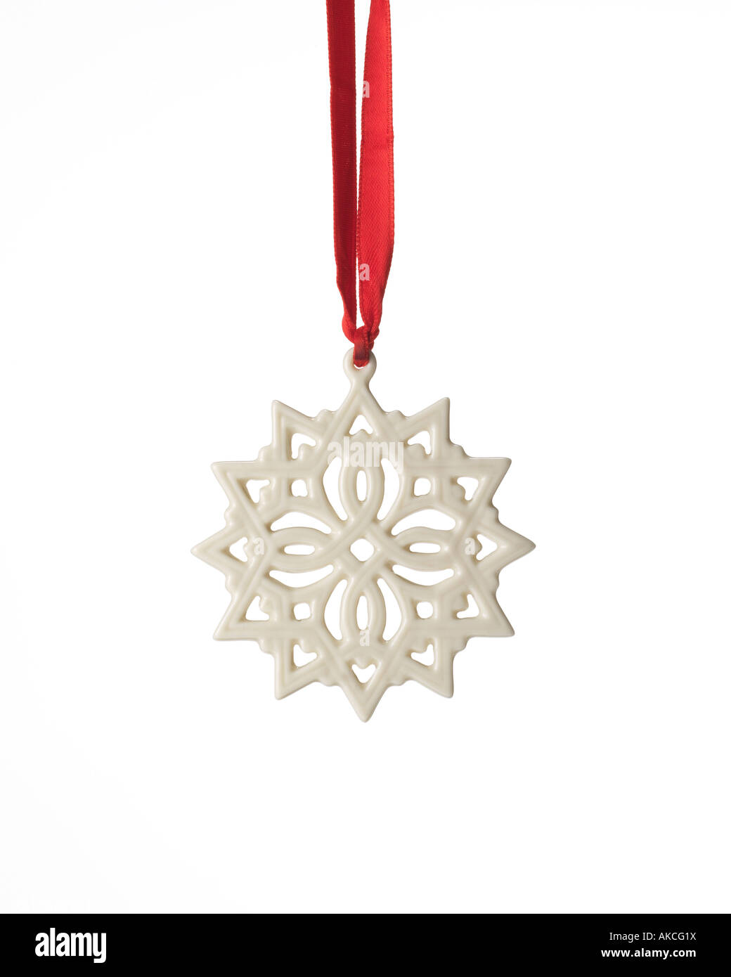 Christmas ornament white stylized porcelain snowflake hanging from red satin ribbon - Stock Image