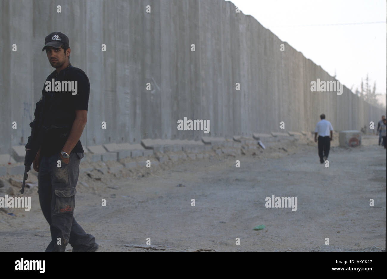 A soldier standing guard by the Apartheid Wall - Stock Image