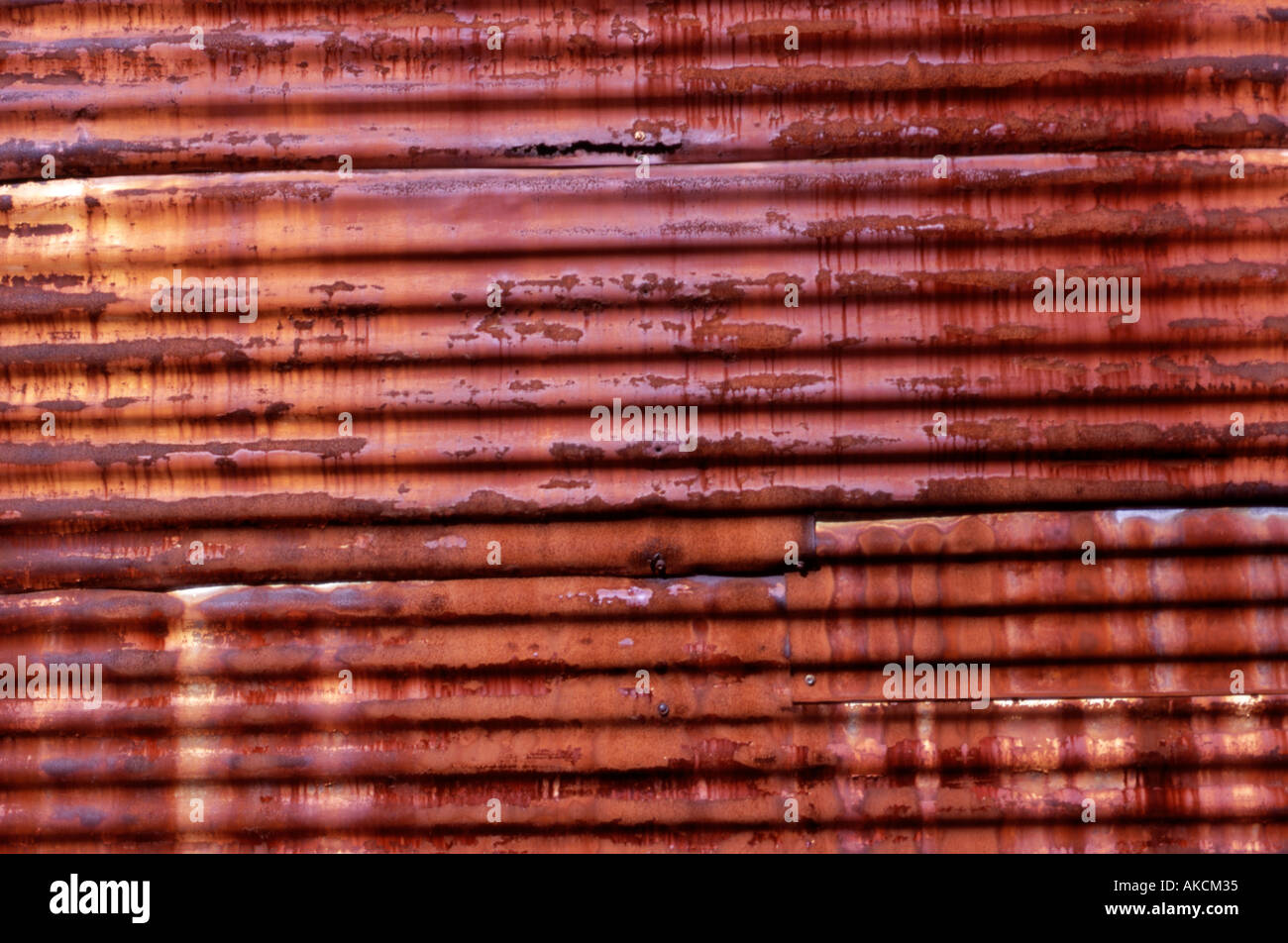 Old warehouse with rusting corrugated iron wall - Stock Image