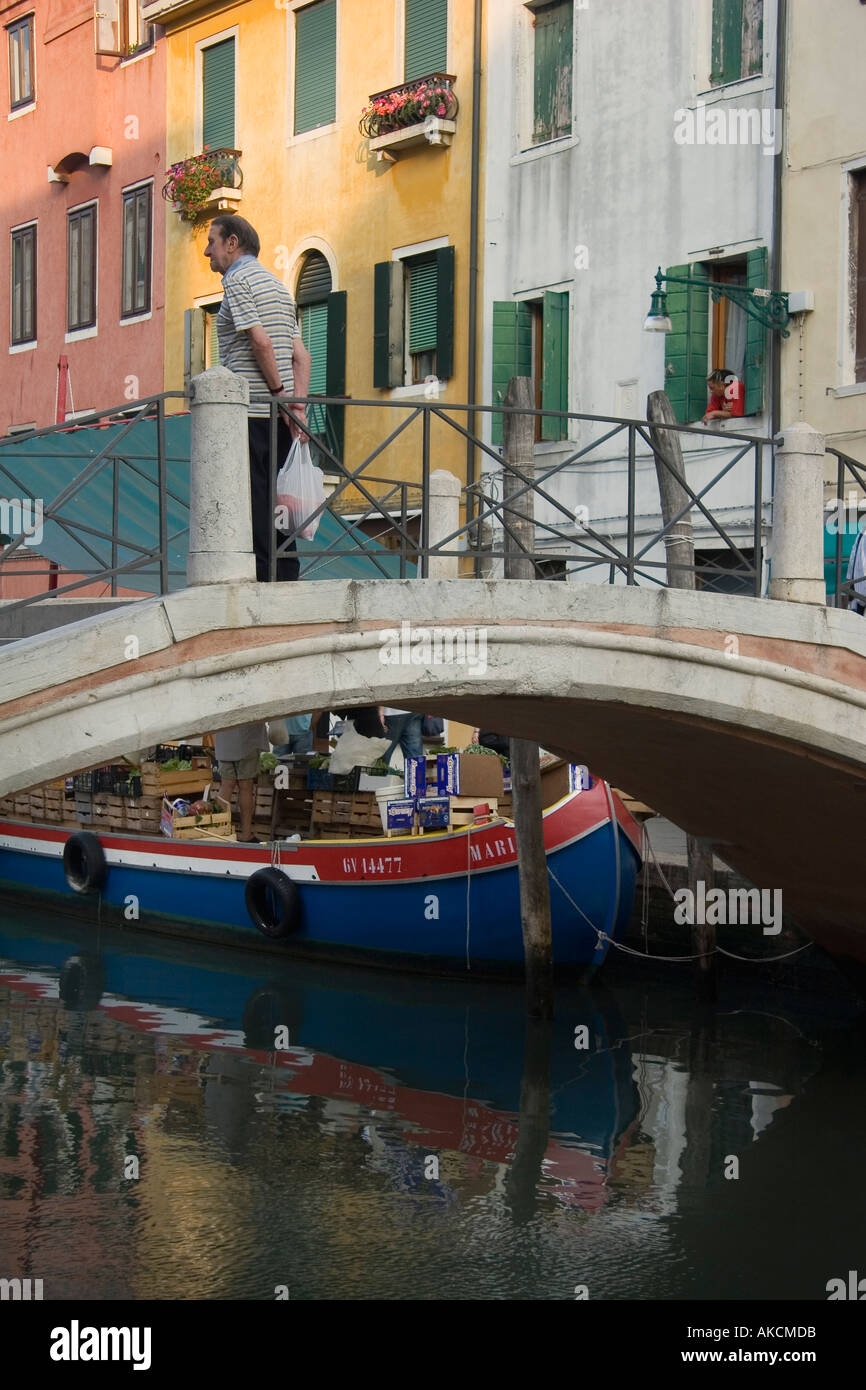 Man standing on bridge watches a produce seller's boat tied up by Ponte Dei Pugni on the Rio S Barnaba Venice Italy - Stock Image