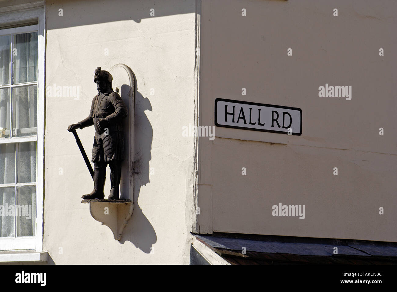 Statue on the facade of a house on the corner of Hig Street and Hall Road Lavenham Suffolk East Anglia UK - Stock Image