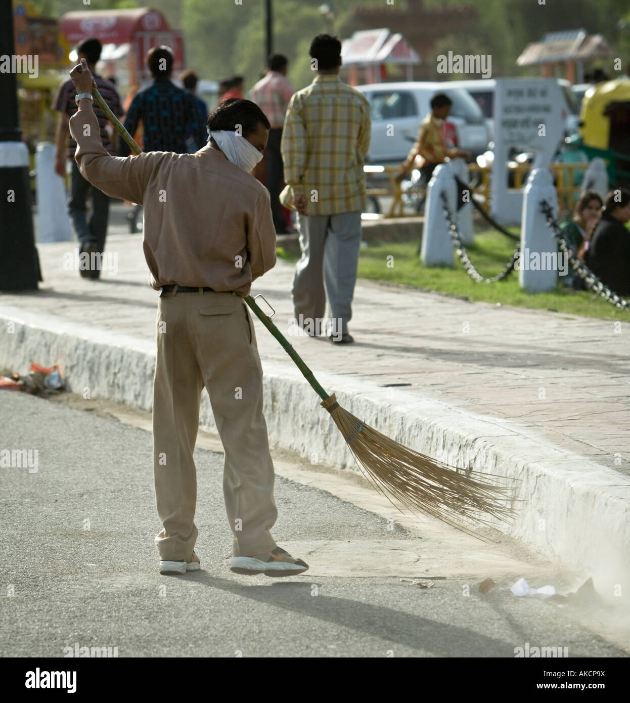 An Indian worker sweeping the road with a traditional broom. He is wearing a makeshift mask  India Gate, Delhi, - Stock Image