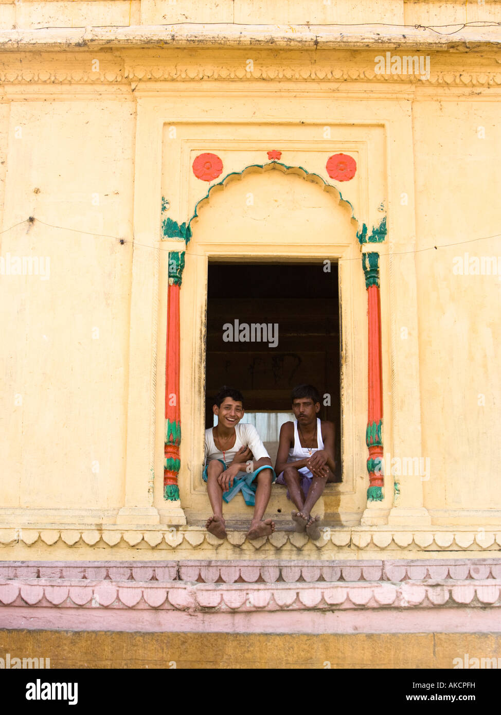 Portrait of two young men sitting in the window of a building in Varanasi Ghat on the banks of the Ganges. Varanasi, - Stock Image