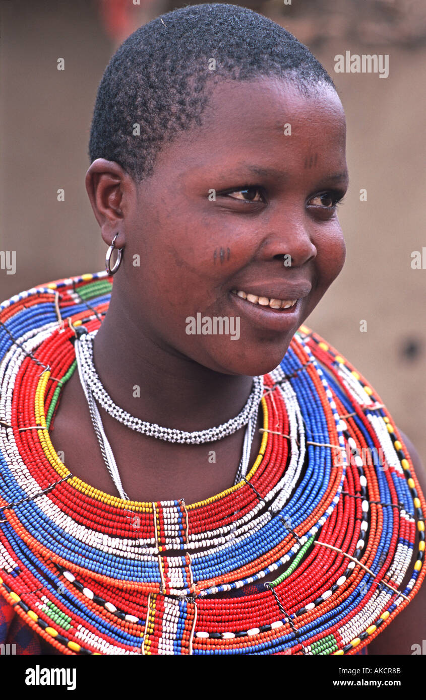 Smiling Masai woman in tribal dress and ornate beadwork necklace North of Arusha en route to southern Kenya Tanzania - Stock Image