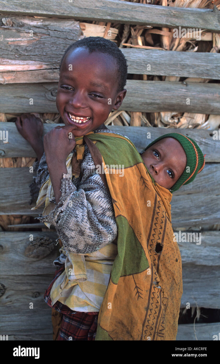Masai girl carrying her baby brother wrapped in a Tanzanian kanga cloth North of Arusha en route to southern Kenya Tanzania - Stock Image