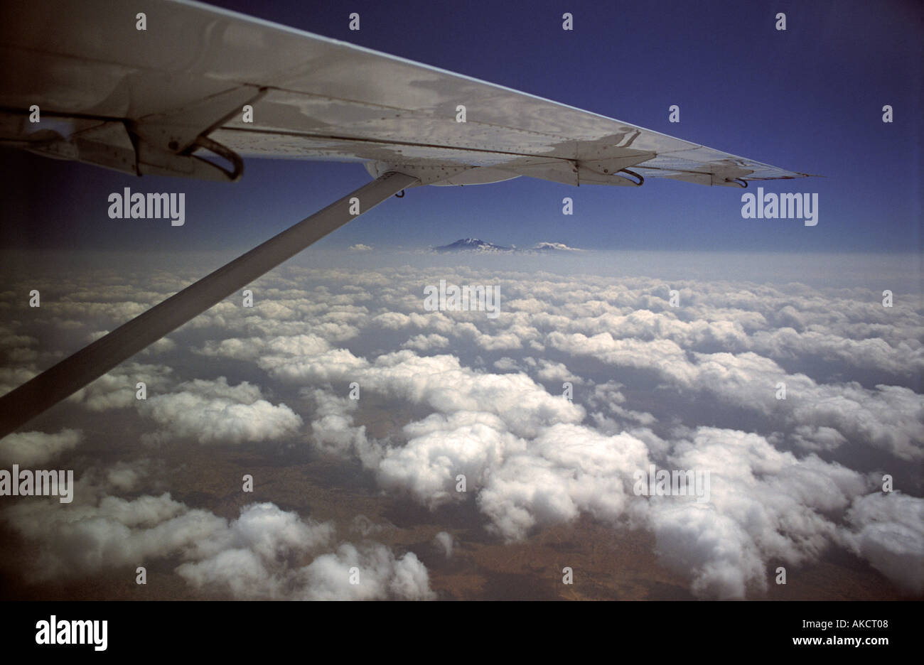 View of Kilimanjaro from a light aircraft Flying to Arusha N Tanzania East Africa Wing of a 13 seater single prop Cessna - Stock Image