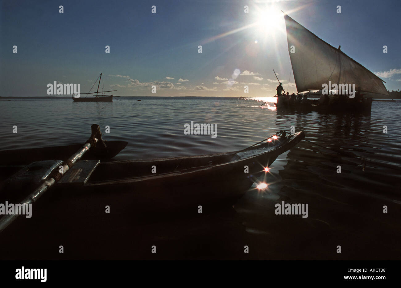 Passenger dhow ferrying people from Chole island to neighbouring Mafia island silhouetted against the rising sun Stock Photo