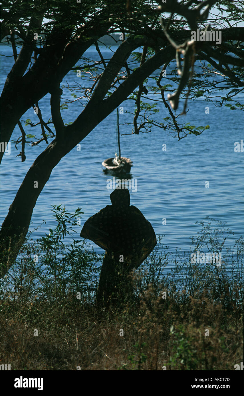 Woman in a kanga cloth standing at the shore on Chole island silhouetted Mafia island Mafia Indian Ocean Tanzania East Africa - Stock Image