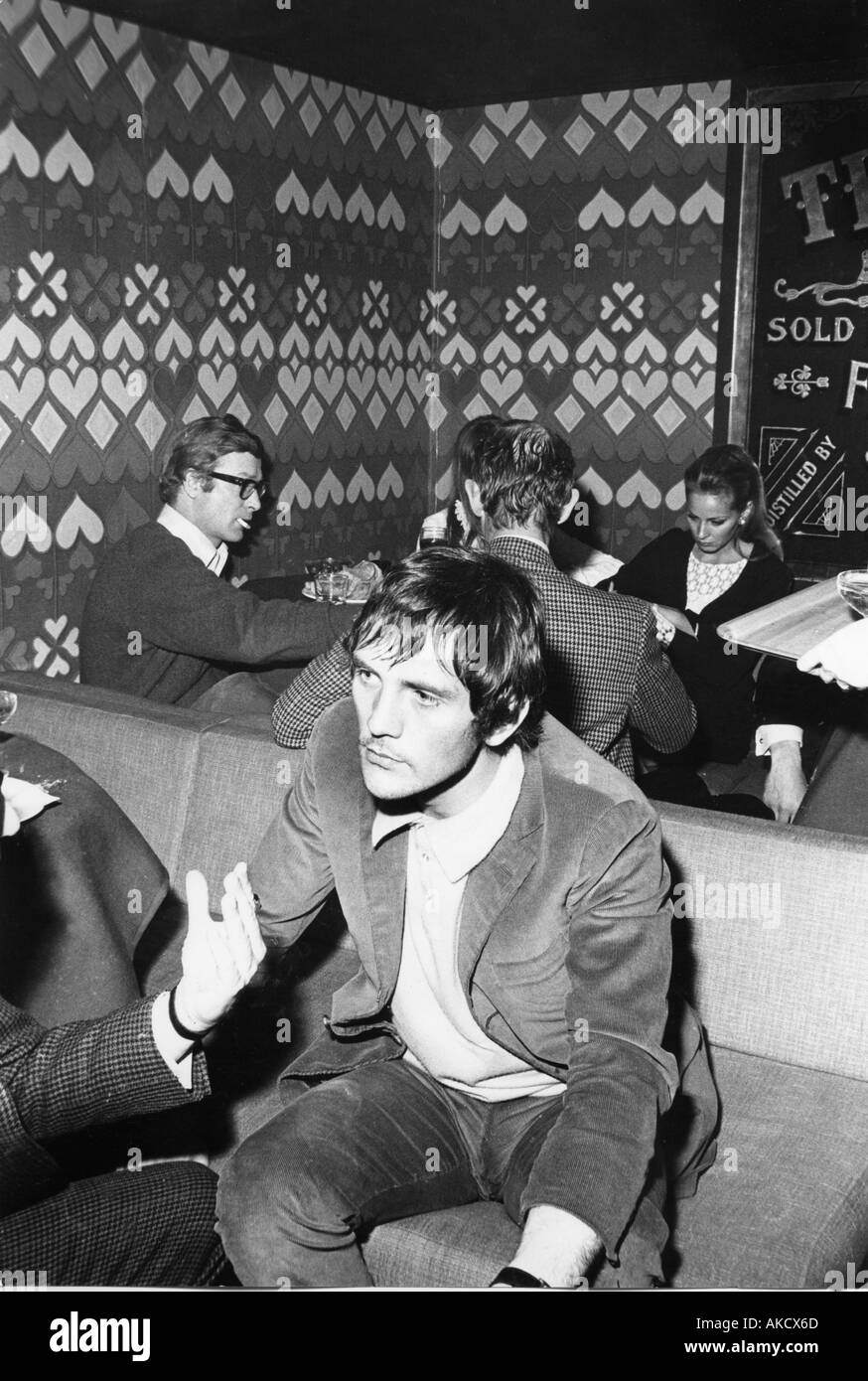 TERENCE STAMP British actor relaxing in a London bar in the 1960s Note Michael Caine in the background - Stock Image