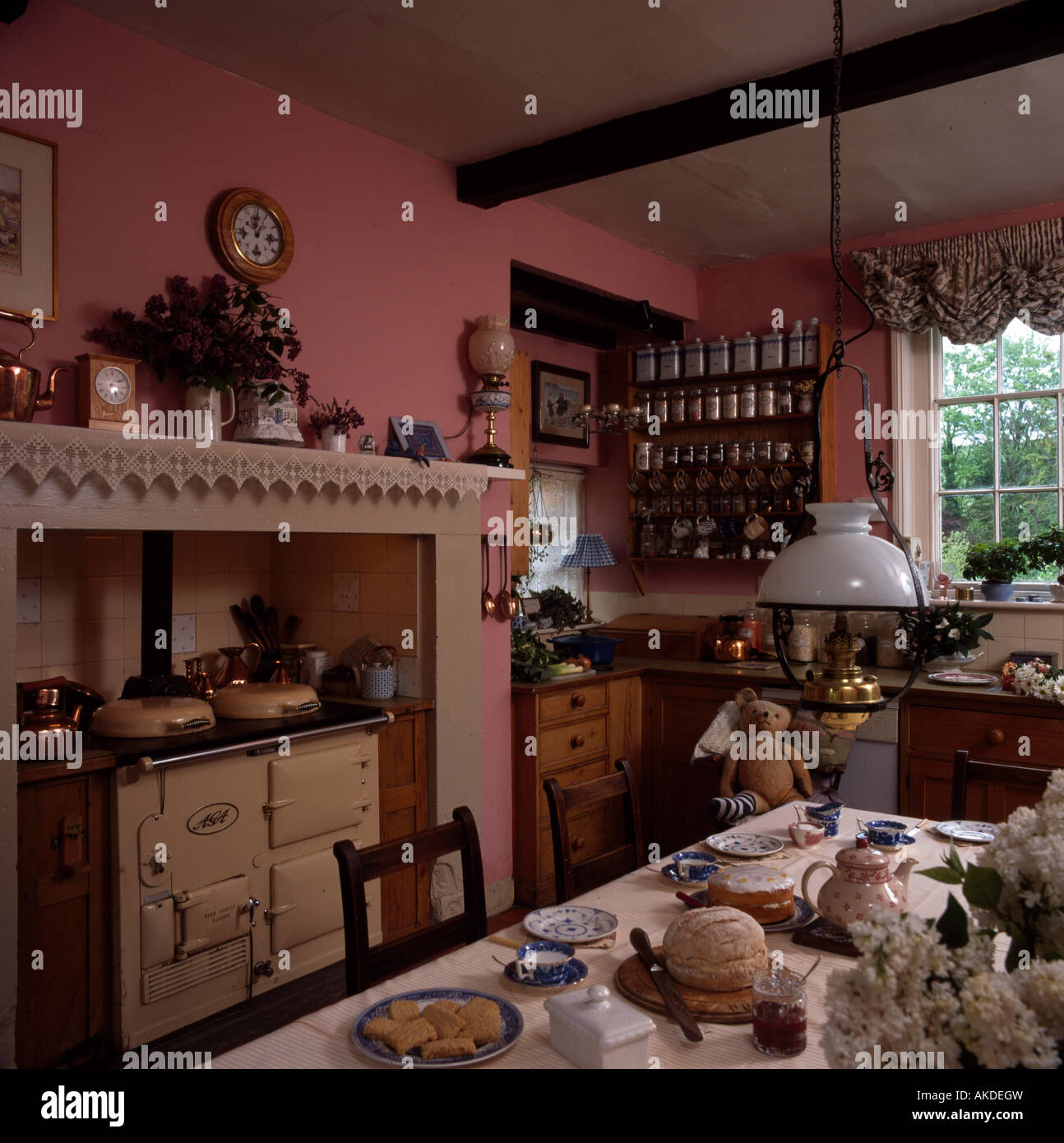 Cream Aga in pink kitchen with table set for tea below Victorian style brass lantern Stock Photo