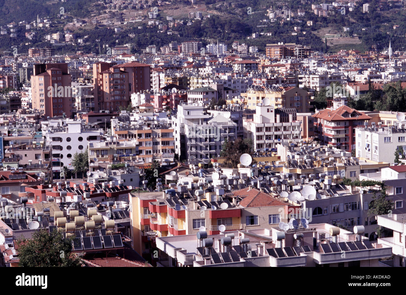 Alanya Turkey city view of buildings and roofs with solar panels for heating satellite dishes and water tanks - Stock Image