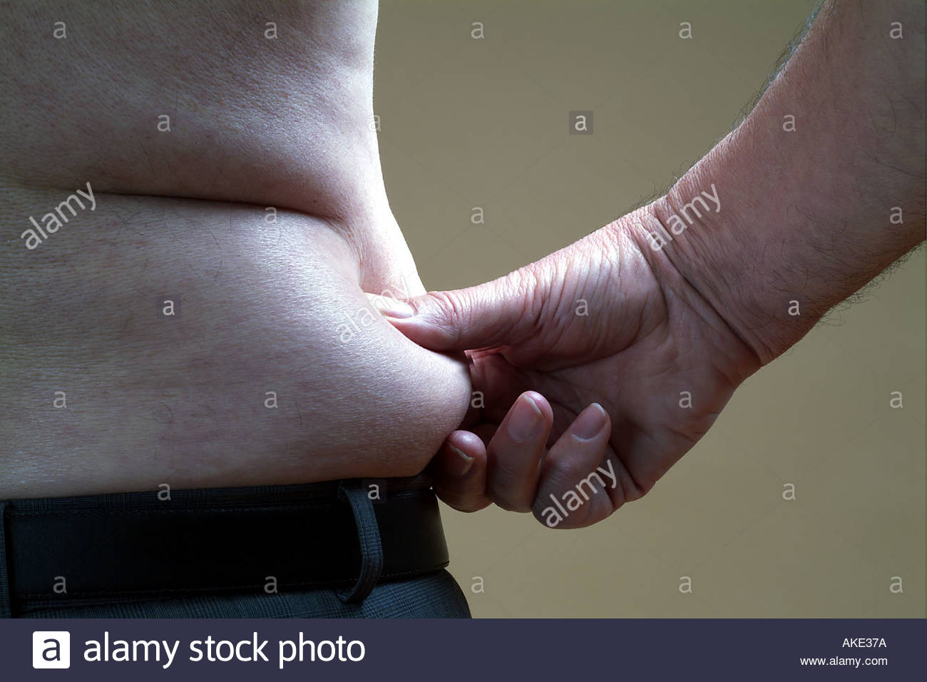 Pinch an inch around the waist of a fat man - Stock Image