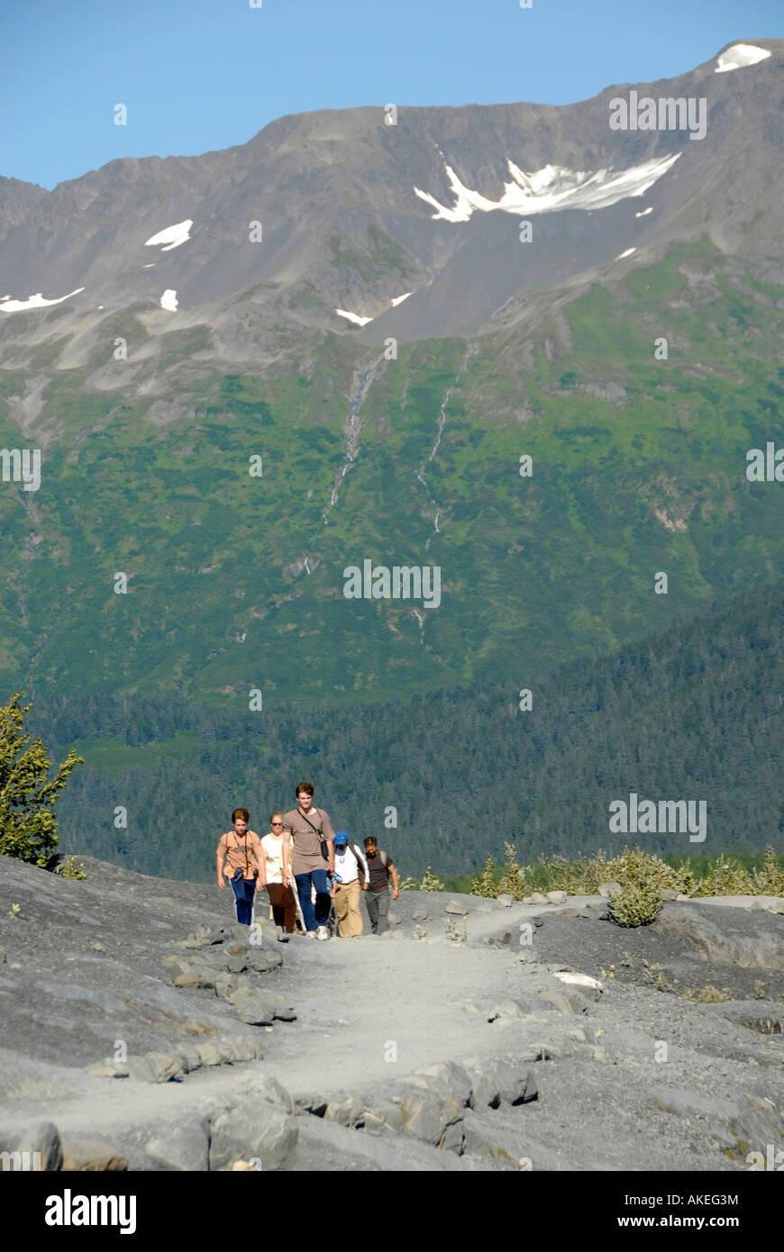 hikers walk trail towards exit glacier in kenai fjords national park