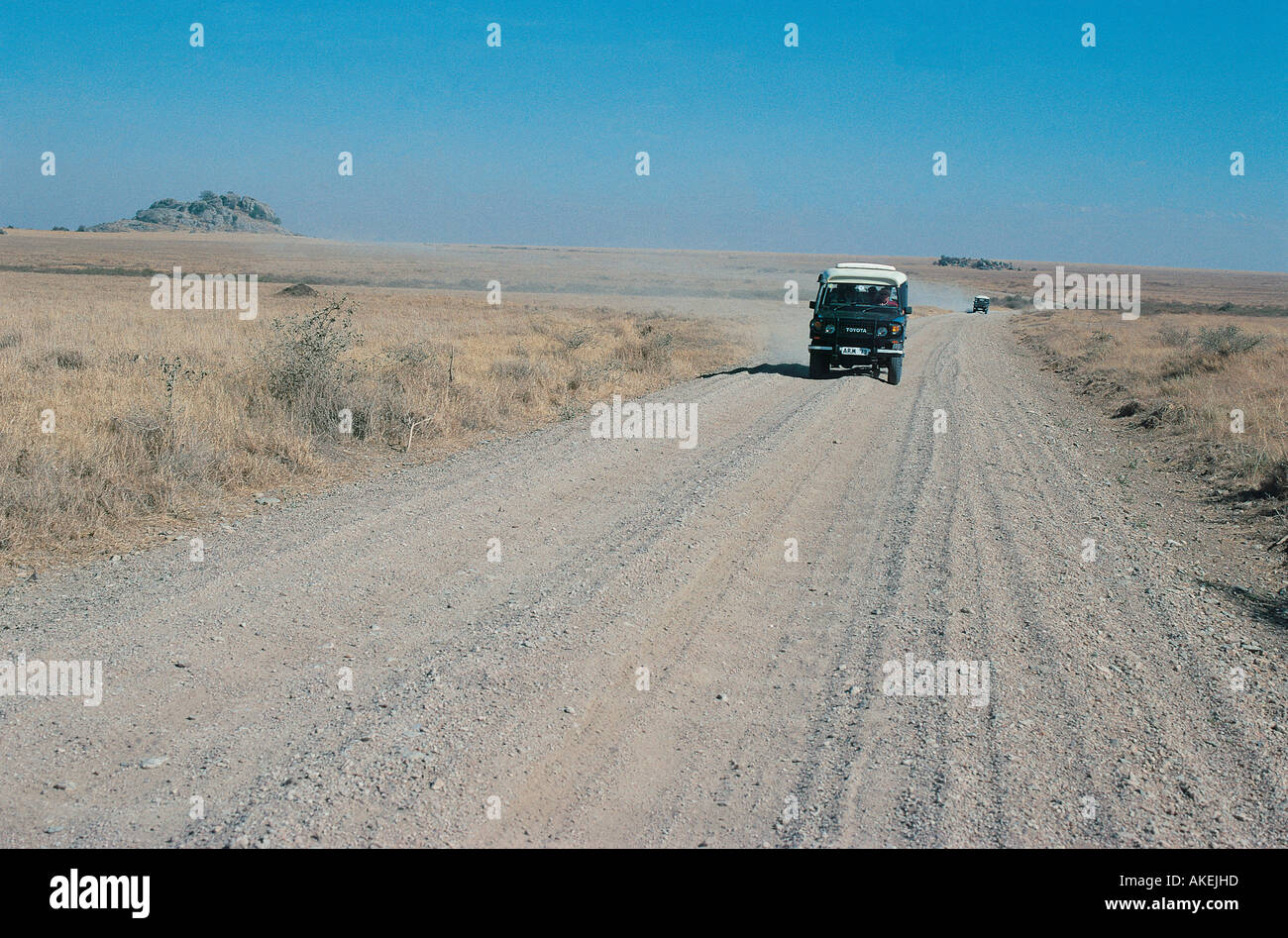 Toyota Landcruiser motoring across the Serengeti Plain in Tanzania East Africa A second car is following in the distance - Stock Image