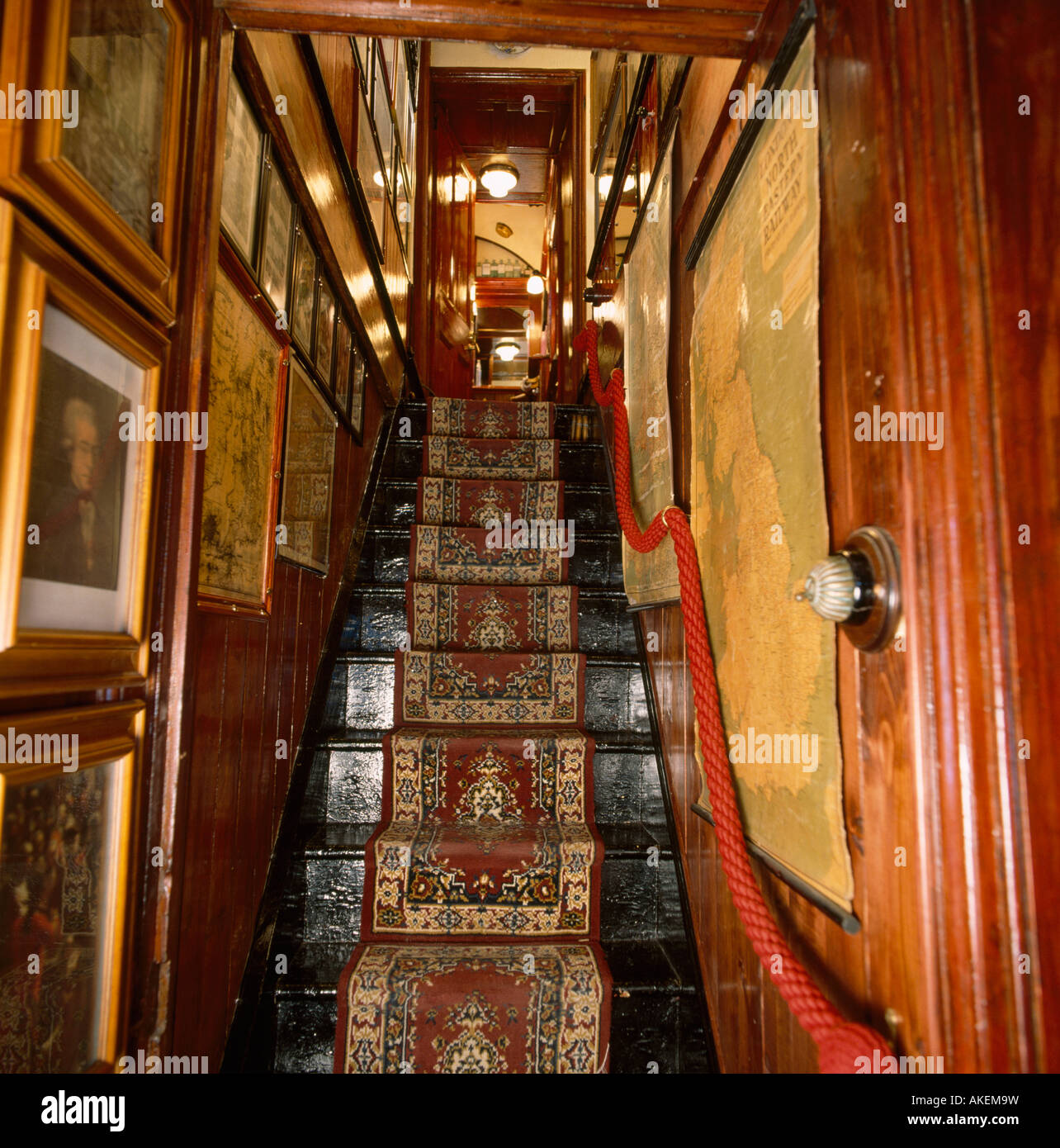 Narrow Black Painted Staircase With Patterned Carpet And Pictures On The  Walls