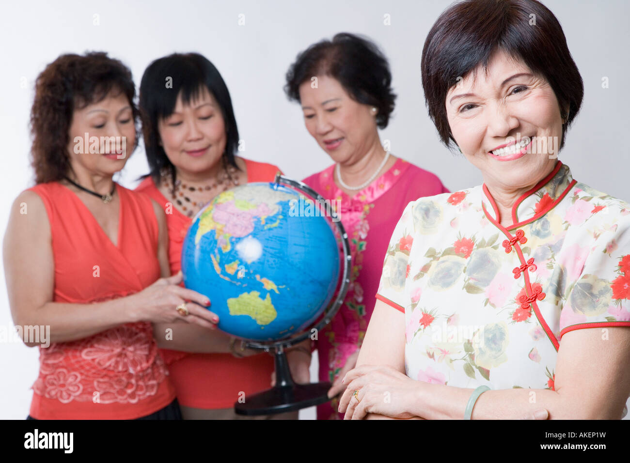 Portrait of a mature woman smiling with her friends looking at a globe - Stock Image