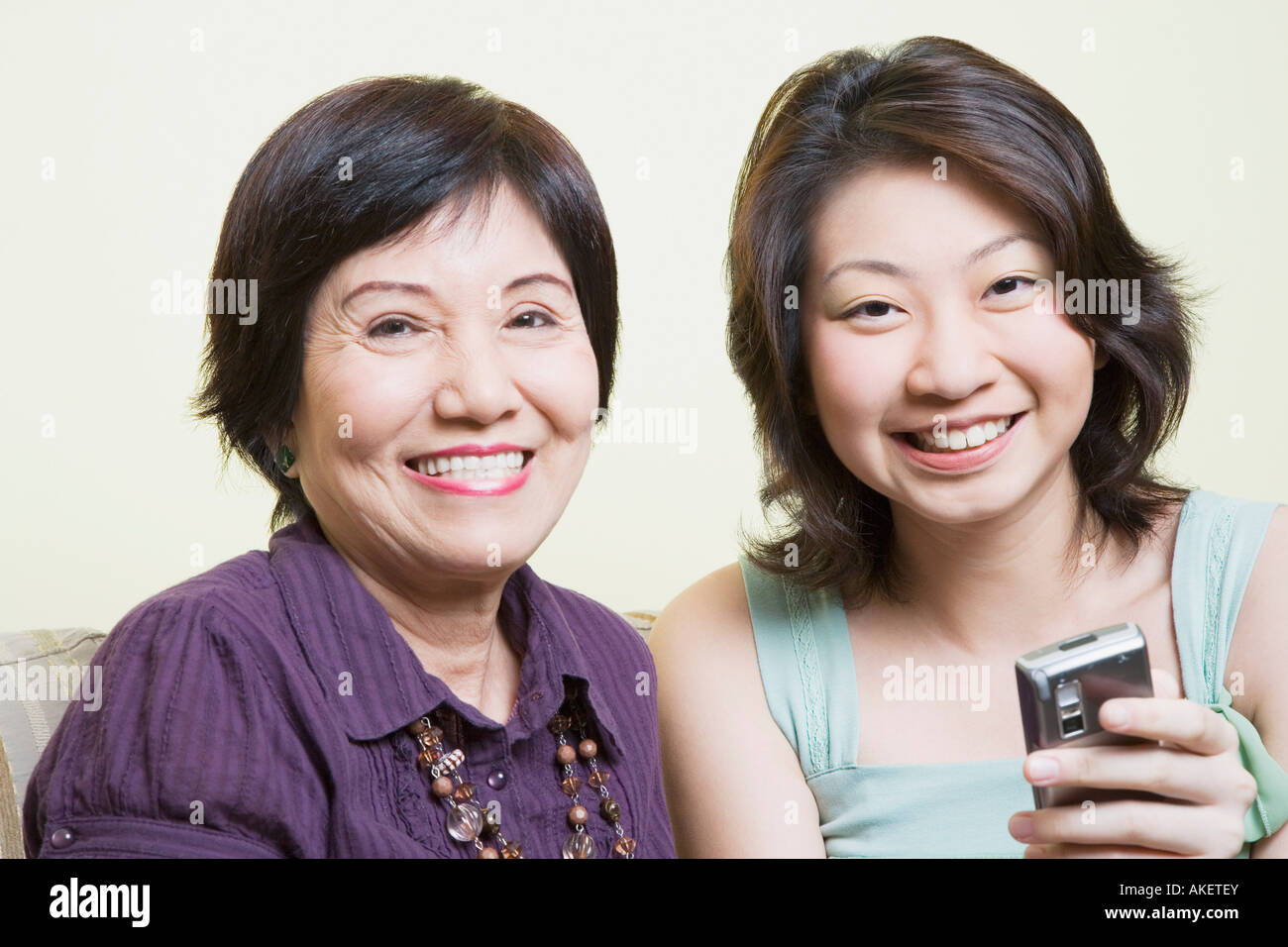 Portrait of a senior woman sitting with her granddaughter and smiling - Stock Image