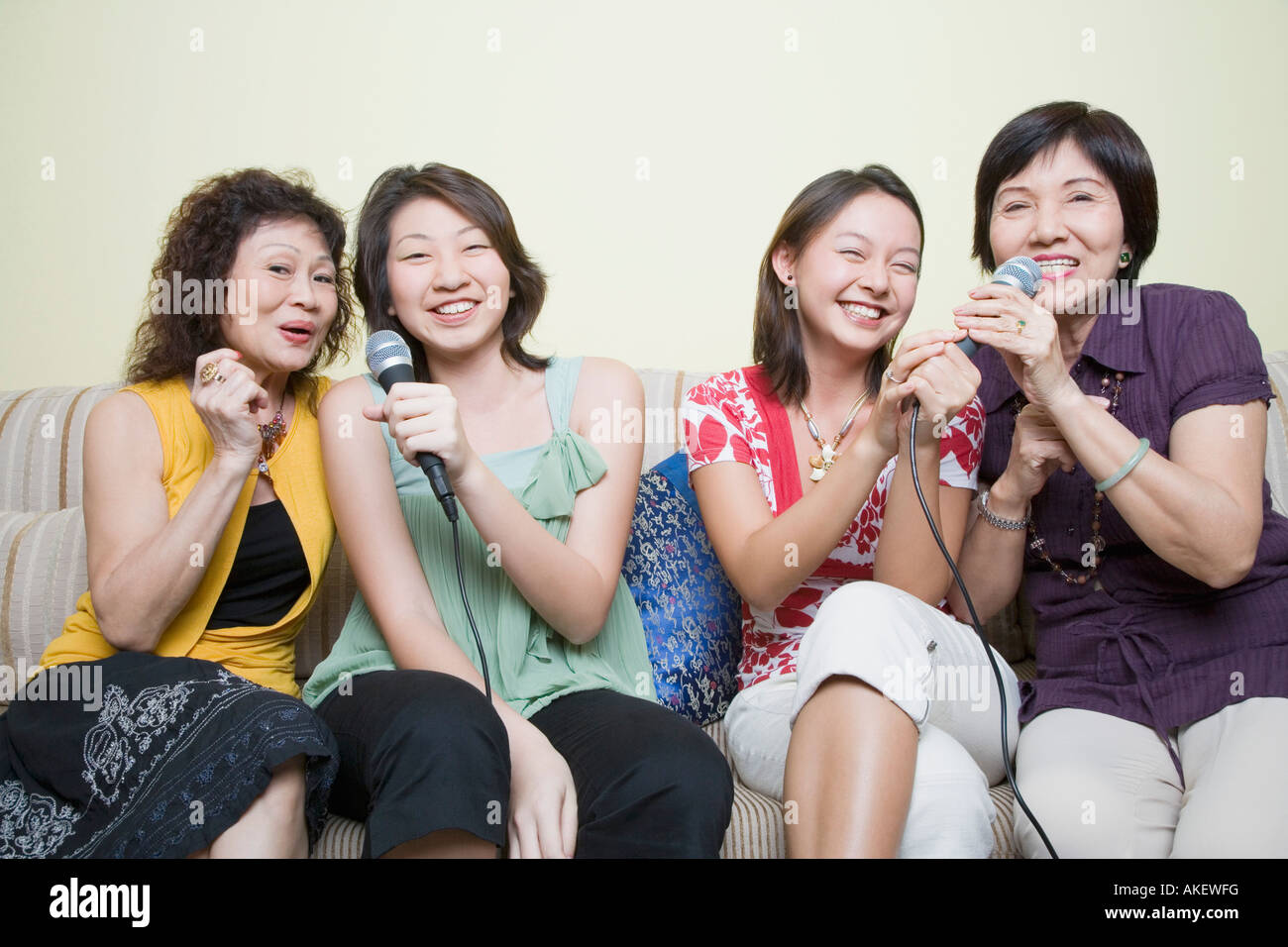 Two young women singing with their grandmothers into microphones - Stock Image